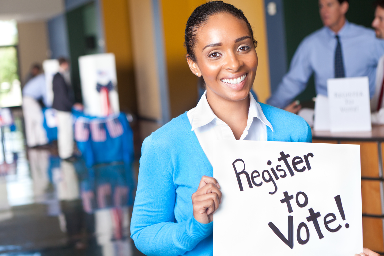 https://www.vivote.gov/sites/default/files/revslider/image/Young-woman-holding-register-to-vote-sign-at-voting-center-155436960_1255x837.jpeg